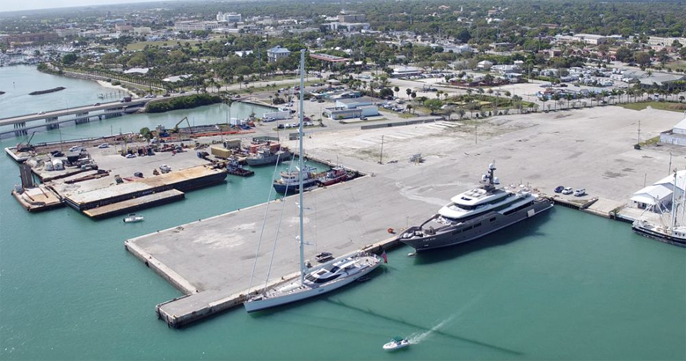 This image shows the Derektor Shipyard from the perspective of the water looking back over the project site. The port is flanked by two mega yachts and existing infrastructure surrounding the port.